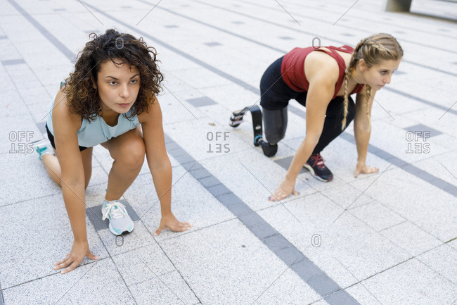 Sportswoman crouching by amputee for sports race on footpath