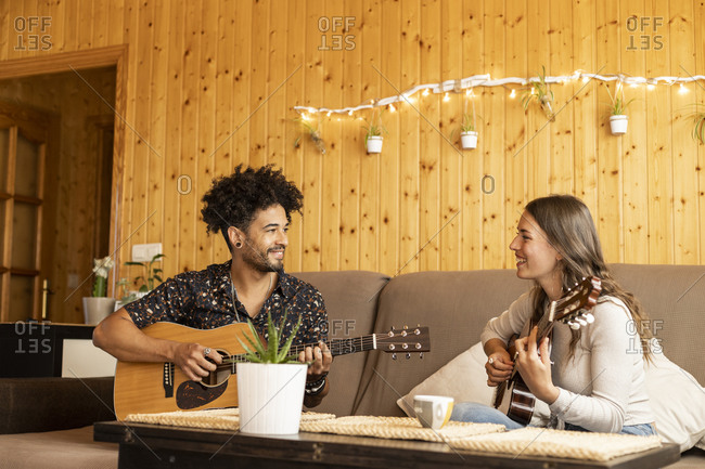 Couple playing guitars while doing rehearsal sitting at home