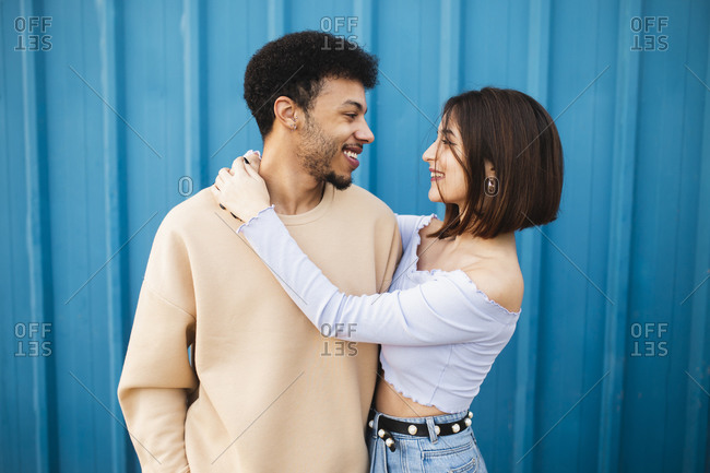 Smiling woman embracing man while standing against blue wall