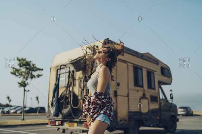 Playful woman tossing hair while standing against motor home
