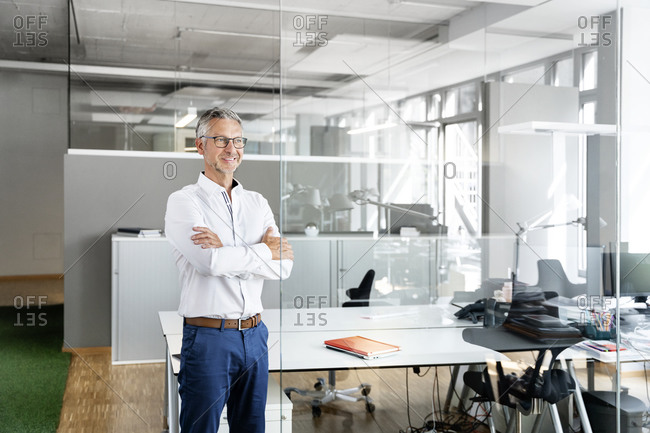 Smiling businessman with arms crossed day dreaming in office