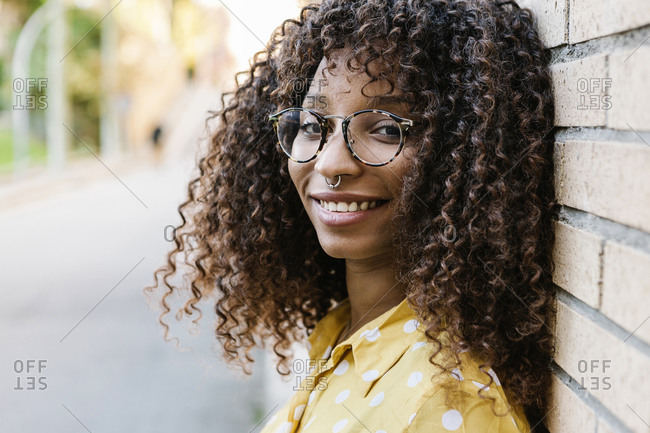Young woman wearing eyeglasses smiling while leaning on wall