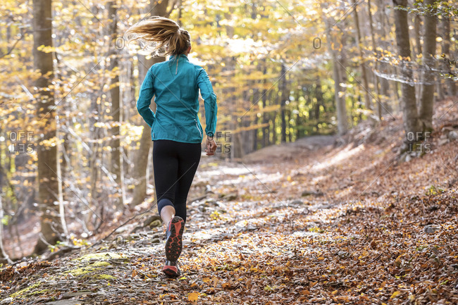 Young athlete exercising while running on footpath in forest