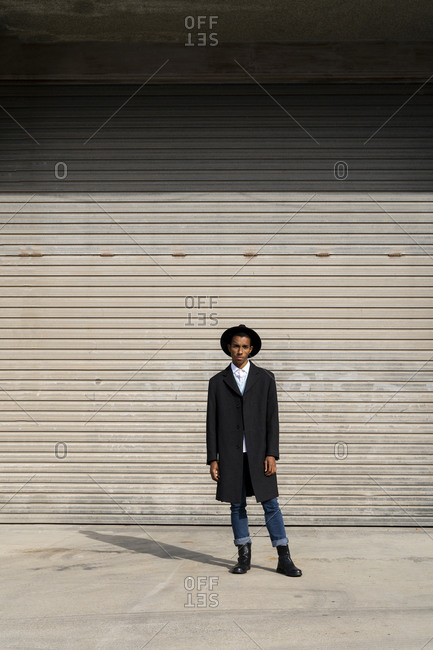 Fashionable young man standing against shutter on sunny day