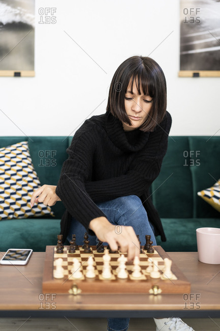 Young woman with concentration playing chess in living room