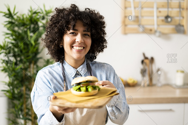 Portrait of young woman holding freshly made vegan sandwich