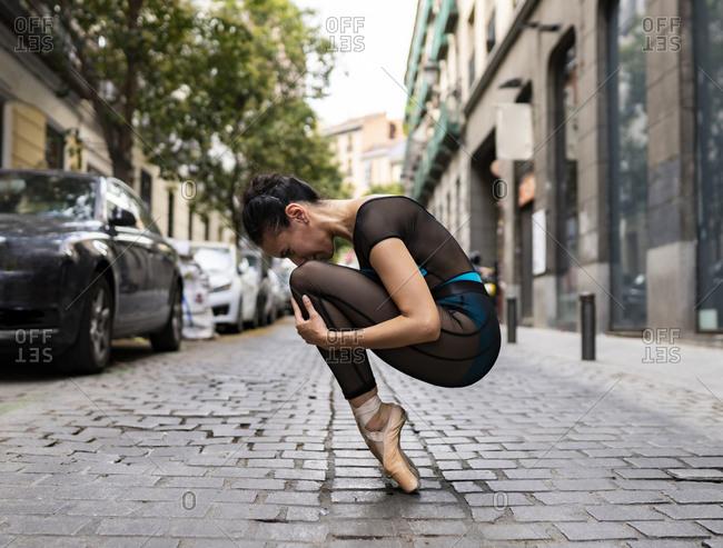 Ballet dancer wearing leotard crouching on footpath in city