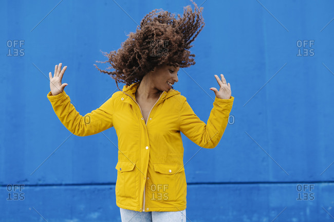 Playful woman tossing hair while standing against blue wall