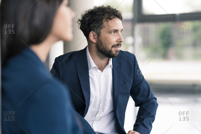 Male entrepreneur looking away by female colleague in lobby