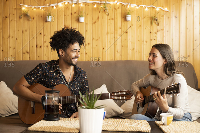 Couple smiling while rehearsing with guitar sitting at home