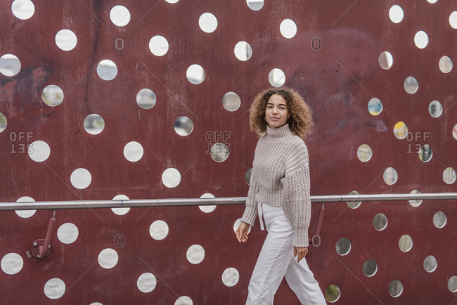 Confident young blond woman walking by maroon metallic wall