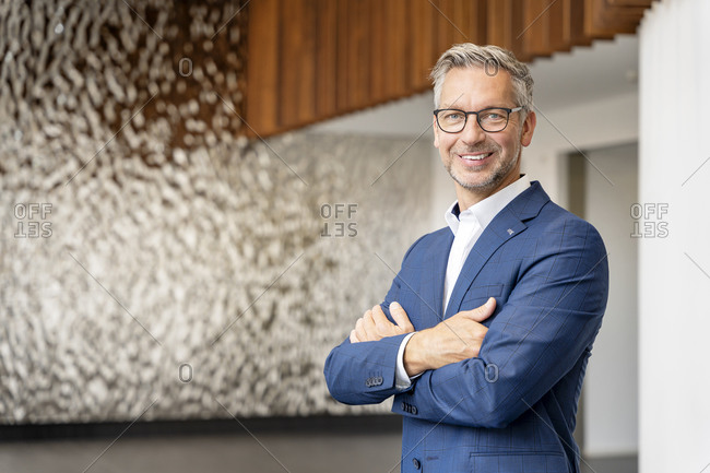 Smiling male entrepreneur with arms crossed in office lobby