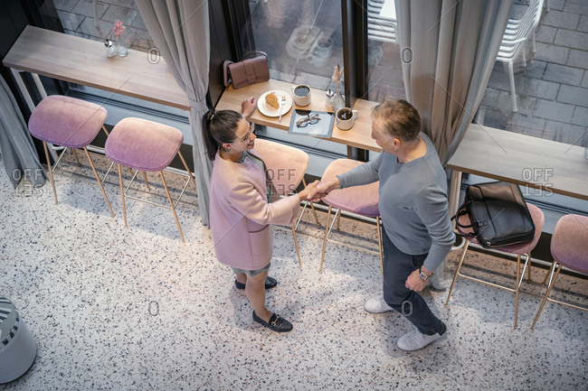 Business people shaking hands while standing at modern cafe