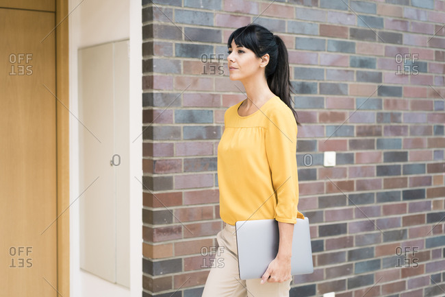 Mature businesswoman with laptop walking by wall in office