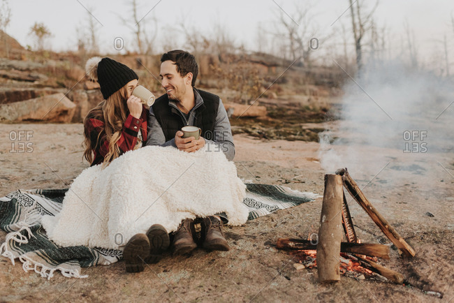 Young couple sitting together in front of smoking campfire