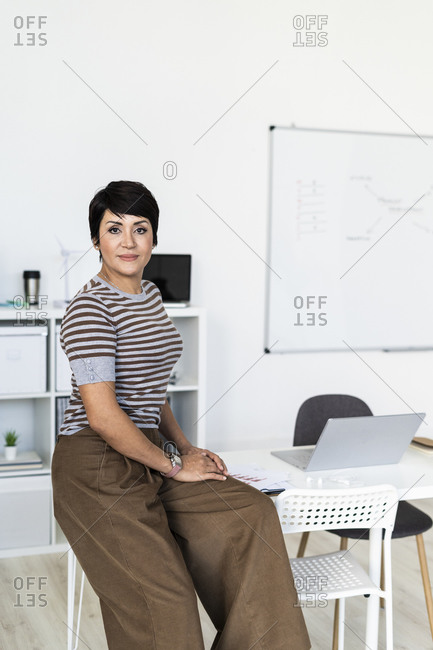 Portrait of businesswoman sitting at edge of office table