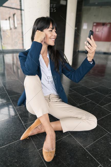 Female entrepreneur taking selfie on smart phone in lobby
