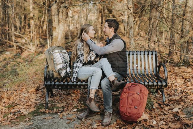 Young couple sitting together on bench during autumn hike