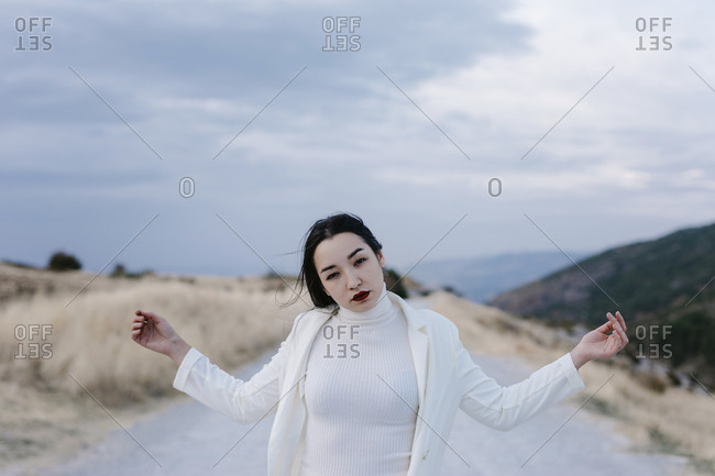 Woman with arms outstretched standing on road against sky