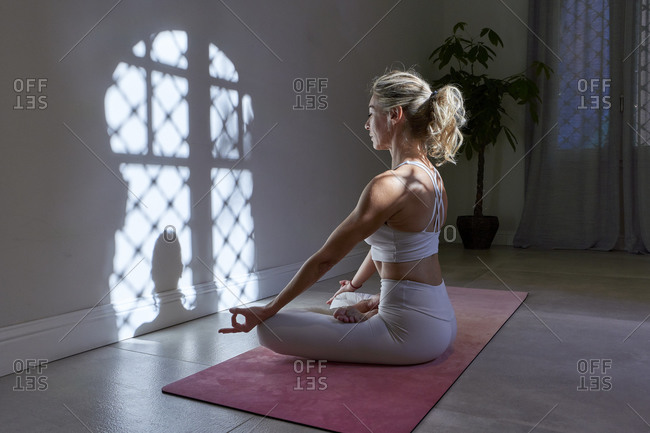 Mature woman meditating sitting in lotus position at home