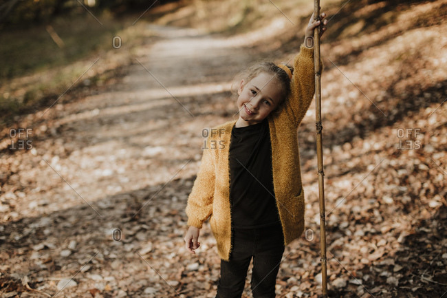 Girl smiling while holding stick standing on forest path
