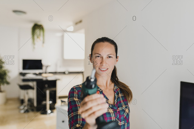 Woman smiling while playing with electric drill at home