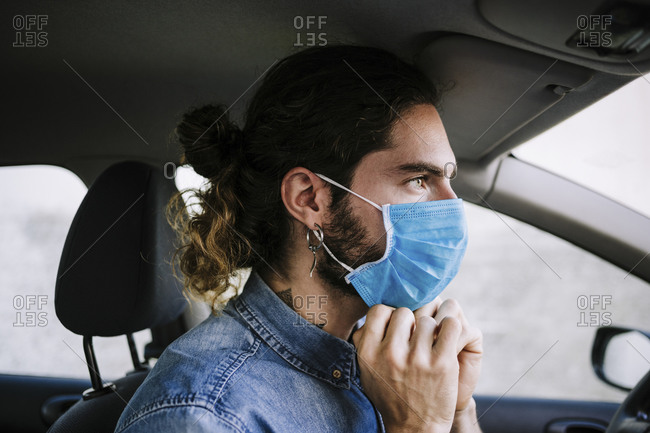 Stylish young man adjusting protective face mask in car