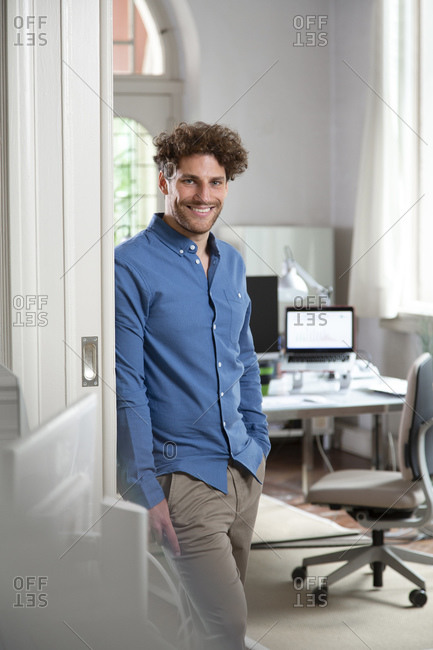 Smiling male professional with hand in pocket at office