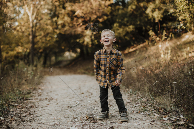 Cheerful boy looking away while standing on forest path