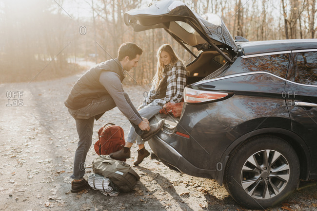 Young couple leaving car before hiking in autumn forest
