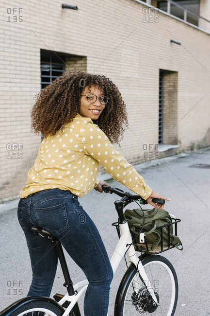 Young woman smiling while standing with bicycle on road