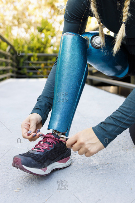 Athlete tying shoelace of prosthetic leg shoe on bridge