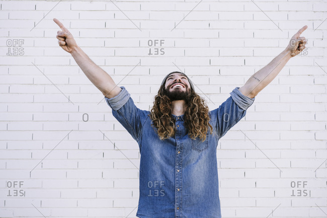 Cheerful young man with arms raised against brick wall