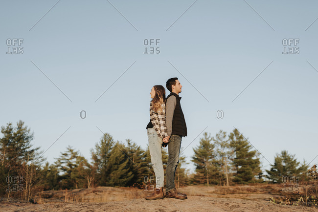 Young couple holding hands while standing back to back