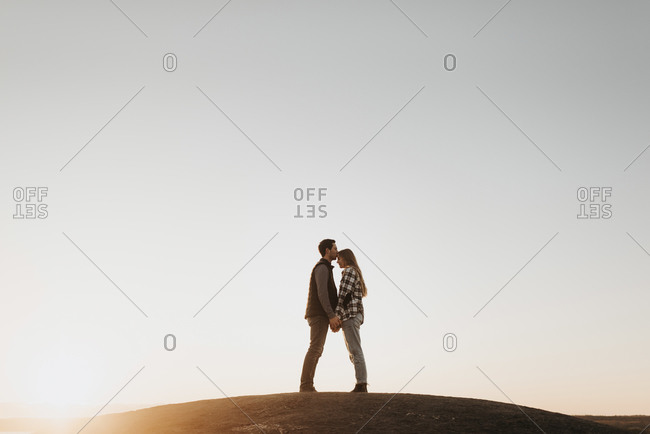 Young couple holding hands against clear sky at sunset