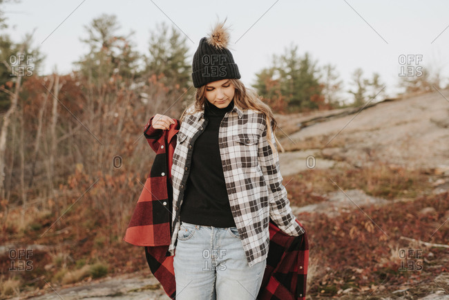 Young woman putting on second shirt during autumn hike
