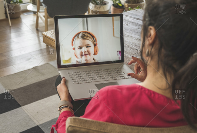 Little girl smiling on laptop screen during video call