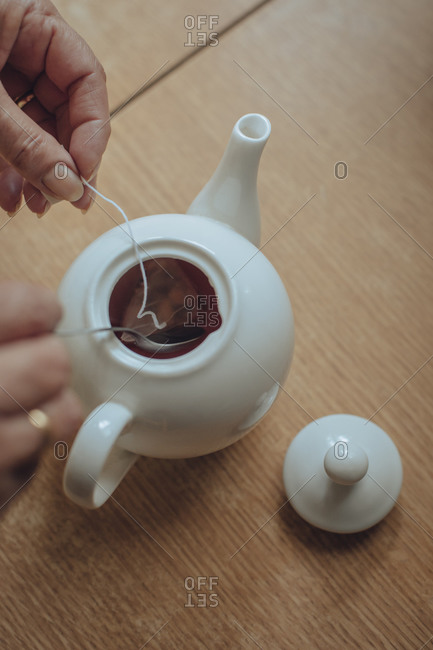 Woman's hands preparing tea in kettle on kitchen table