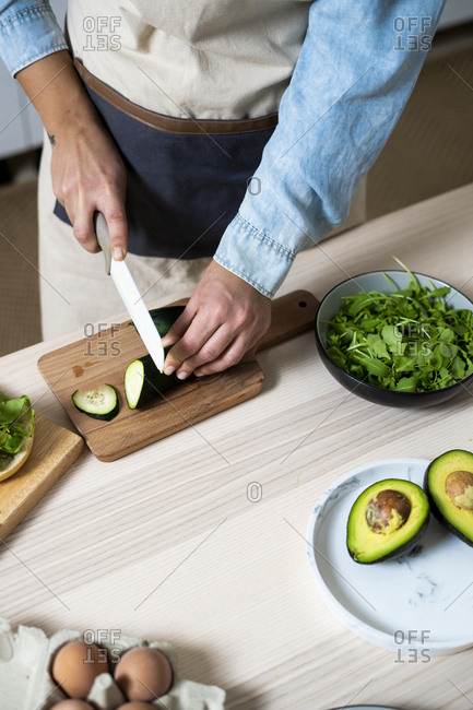 Mid section of woman slicing cucumber on cutting board