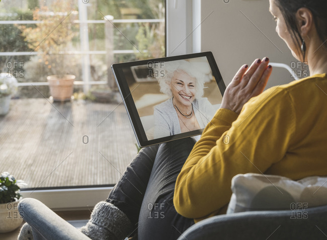 Two women talking during video call on digital tablet