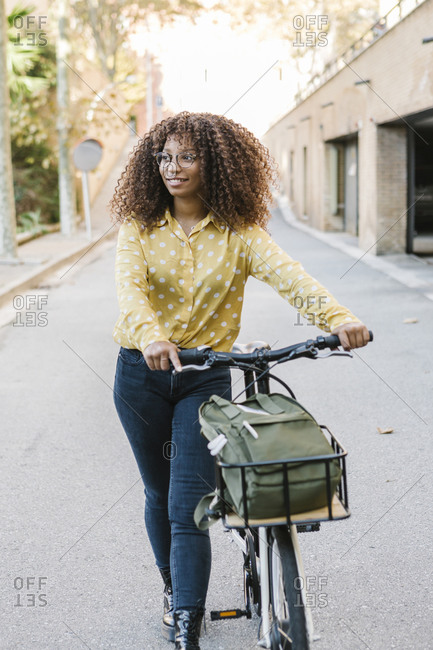 Woman looking away while walking with bicycle on road