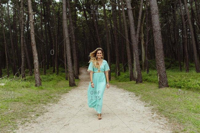 Mid adult woman smiling while walking on forest path
