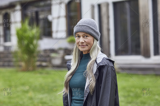 Confident mature woman wearing knit hat in back yard