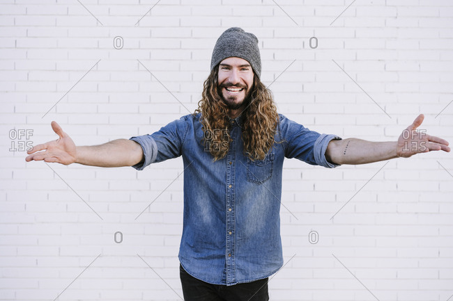Happy young man with arms raised against brick wall
