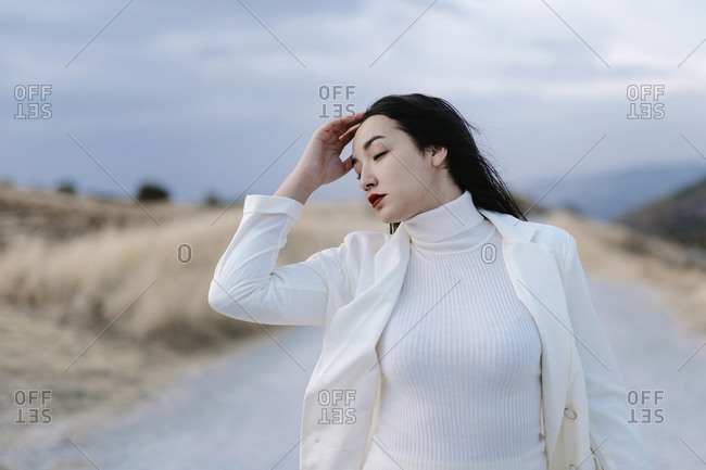 Young woman with head in hands standing against sky