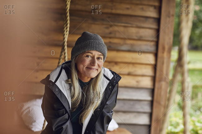 Smiling mature woman wearing knit hat in back yard
