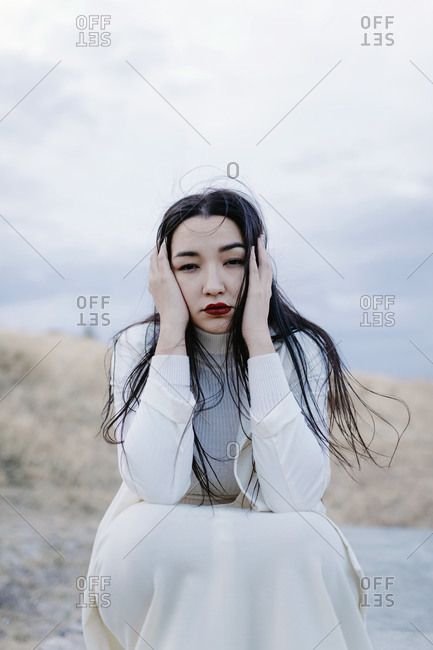 Sad woman with head in hands crouching against sky