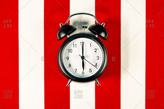 Alarm clock lying on white and red striped pattern