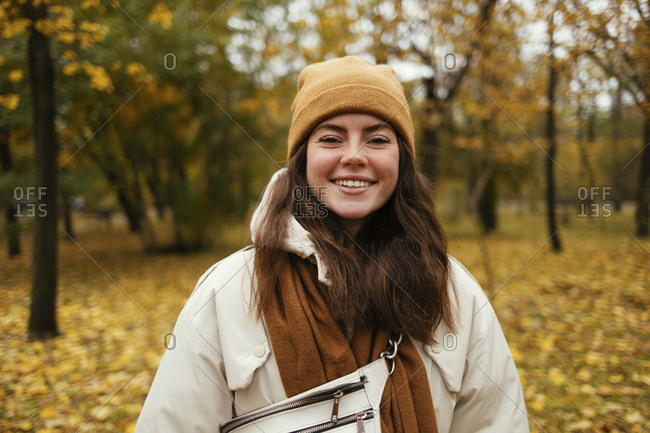 Happy young woman in warm clothing in autumn park