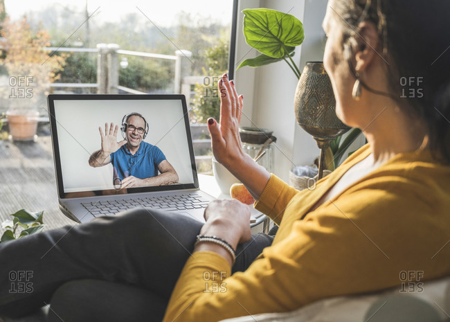 Man and woman waving during video call on laptop
